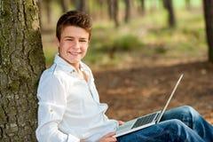 Ritratto del ragazzo teenager con il computer portatile. Immagine Stock Libera da Diritti