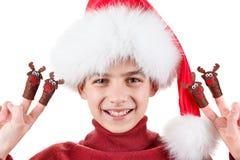 Ritratto del ragazzo teenager felice in cappello di Santa con il giocattolo dei cervi su isolato su bianco Immagini Stock Libere da Diritti