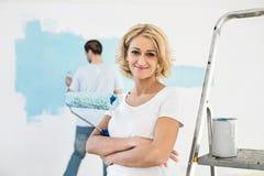 Ritratto del rullo di pittura della tenuta della donna con la parete della pittura dell'uomo nel fondo Fotografia Stock Libera da Diritti