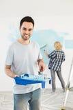 Ritratto del rullo e del vassoio di pittura della tenuta dell'uomo con la parete della pittura della donna nel fondo Immagini Stock
