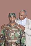 Ritratto del soldato afroamericano degli Stati Uniti Marine Corps del maschio con il padre sopra fondo marrone Fotografia Stock