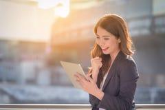 Ritratto del sorriso felice della donna di affari che sembra compressa digitale sopra fotografie stock libere da diritti