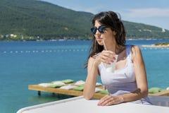 Ritratto del succo bevente della giovane donna sulla spiaggia Fotografia Stock