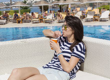 Ritratto del succo bevente della giovane donna sullo stagno Fotografia Stock Libera da Diritti