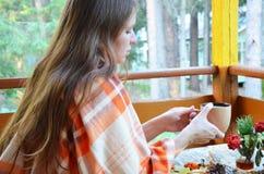 Ritratto del tè bevente della bella ragazza bionda nel giardino di autunno avvolga in un generale, primo piano fotografia stock libera da diritti