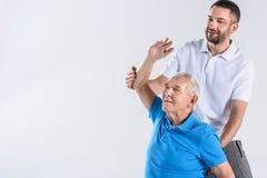 ritratto del terapista di riabilitazione che aiuta allungamento dell'uomo senior Fotografia Stock