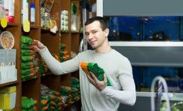 Ritratto del tipo che seleziona l'alimento del veterinario nel petshop Fotografie Stock Libere da Diritti