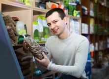 Ritratto del tipo che seleziona l'alimento del veterinario nel petshop Fotografia Stock