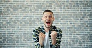 Ritratto del tipo fortunato che alza i pugni che celebrano successo sul fondo del muro di mattoni archivi video