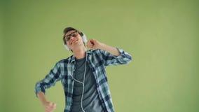 Ritratto del tipo moderno che ascolta la musica in cuffie e che balla divertendosi stock footage