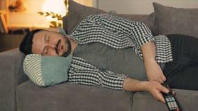 Ritratto del tipo nei chothes casuali che dorme sullo strato a casa che giudica TV a distanza stock footage