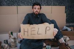 Ritratto del tipo senza tetto che si siede sul cartone e che tiene un cartone di aiuto in mani Sta esaminando diritto la macchina Immagini Stock