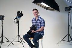 Ritratto del tiro di foto maschio di In Studio For del fotografo con la macchina fotografica ed il materiale di illuminazione fotografia stock