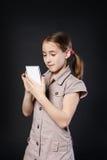 Ritratto del touch screen serio della ragazza sul telefono cellulare Fotografia Stock