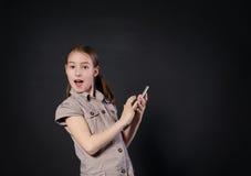 Ritratto del touch screen sorpreso della ragazza sul telefono cellulare Immagine Stock