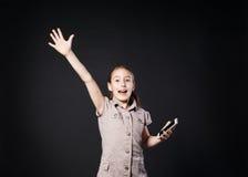 Ritratto del touch screen sorpreso della ragazza sul telefono cellulare Immagini Stock