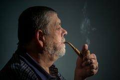 Ritratto del tubo di tabacco da fumo barbuto caucasico dell'uomo contro fondo scuro Fotografia Stock