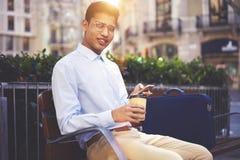 Ritratto del turista maschio sorridente che gode del caffè e che cerca i nuovi posti interessanti Fotografia Stock