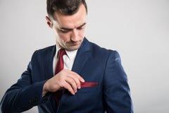 Ritratto del vestito d'uso dell'uomo di affari che sistema la tasca del rivestimento fotografia stock