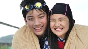 Ritratto del vestito di nuoto d'uso asiatico felice della ragazza e del ragazzo che esamina macchina fotografica