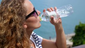 Ritratto dell'acqua potabile della giovane donna all'aperto stock footage