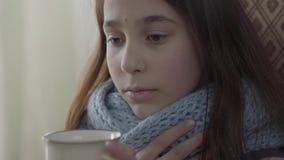 Ritratto dell'adolescente avvolto in sciarpa calda che tiene una tazza di t? caldo in mani La ragazza ritiene cattiva, ? malata e archivi video