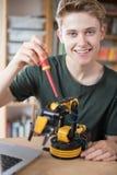 Ritratto dell'adolescente che costruisce braccio robot alla scuola fotografie stock