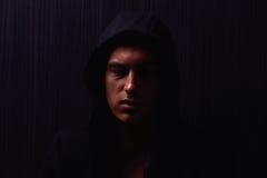 Ritratto dell'adolescente con l'espressione seria e la maglia con cappuccio nera Fotografie Stock Libere da Diritti