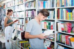 Ritratto dell'adolescente felice che esamina libro aperto Fotografia Stock