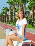 Ritratto dell'adolescente mentre sedendosi sul banco bianco Fotografia Stock