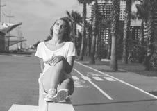 Ritratto dell'adolescente mentre sedendosi sul banco bianco Fotografie Stock