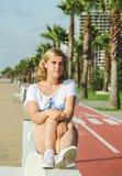 Ritratto dell'adolescente mentre sedendosi sul banco bianco Fotografia Stock Libera da Diritti