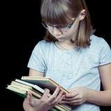 Ritratto dell'adolescente in vetri con la pila di libri isolati su fondo nero Fotografie Stock