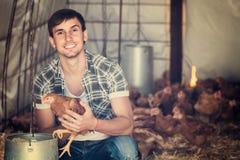 Ritratto dell'agricoltore dell'uomo con il pollo sull'azienda avicola all'interno Immagini Stock