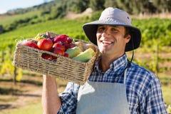 Ritratto dell'agricoltore felice che tiene un canestro degli ortaggi freschi Immagine Stock
