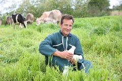 Ritratto dell'agricoltore fiero nel fild di erba con le mucche Fotografie Stock