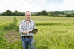 Ritratto dell'agricoltore Holding un computer della compressa in un campo Immagine Stock