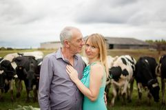 Ritratto dell'agricoltore senior bello e sua giovane della moglie bionda che abbracciano davanti alle loro mucche in bianco e ner fotografia stock libera da diritti