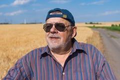 Ritratto dell'agricoltore senior sorridente che sta al bordo del giacimento di grano e soddisfatto con il raccolto futuro Immagini Stock