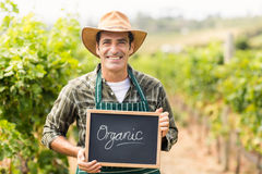 Ritratto dell'agricoltore sorridente che tiene un segno organico Immagini Stock Libere da Diritti
