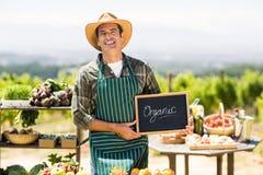 Ritratto dell'agricoltore sorridente che tiene un segno organico Fotografie Stock
