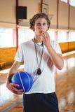Ritratto dell'allenatore di pallacanestro maschio con il fischio e la palla Fotografia Stock