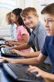 Ritratto dell'allievo elementare maschio nella classe del computer Fotografia Stock