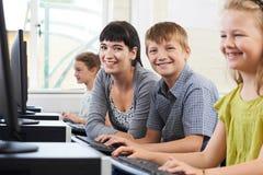 Ritratto dell'allievo elementare maschio nella classe del computer con la femmina Fotografie Stock
