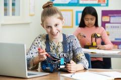 Ritratto dell'allievo femminile nella lezione di scienza che studia robotica Fotografia Stock