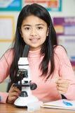 Ritratto dell'allievo nella classe di scienza facendo uso del microscopio Immagine Stock