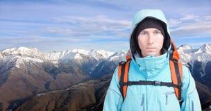 Ritratto dell'alpinista del giovane nelle montagne di inverno Cielo blu e nubi bianche Immagini Stock