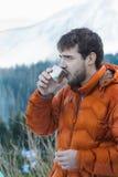 Ritratto dell'alpinista di riposo con la boccetta di vuoto calda del metallo della bevanda al fondo nevoso delle montagne Fotografia Stock