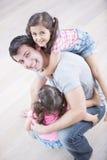 Ritratto dell'angolo alto delle ragazze di trasporto del padre allegro a casa Fotografia Stock