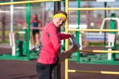 Ritratto dell'atleta femminile caucasico felice Having Legs Muscles che allunga gli esercizi vicino all'istruttore Outdoors Fotografia Stock
